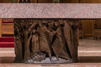 The pedestal is encircled by a bronze bas-relief depicting Old Testament scenes of sacrificial offerings and preparation.